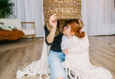 Mère et fille rousse jouant le cache-cache à la maison, utilisant le grand panier photographie stock
