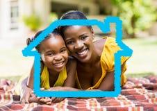 Mère et fille s'étendant en parc contre le contour de maison à l'arrière-plan Images libres de droits