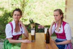 Mère et fille s'asseyant à une table dans le dirndl devant un g Photo stock