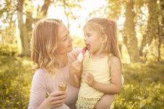 Mère et fille s'asseyant sur l'herbe et mangeant la crème glacée  Images libres de droits