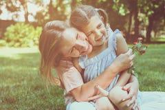 Mère et fille s'asseyant sur l'herbe pour embrasser Participation de mère Photos stock