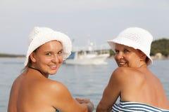 Mère et fille s'asseyant sur le bord de mer, plage ensoleillée Photographie stock