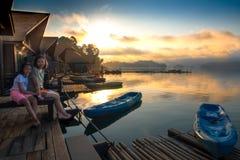 Mère et fille s'asseyant sur le lac naturel de radeau pendant le matin Image libre de droits