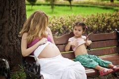 Mère et fille s'asseyant sur un banc de parc photo libre de droits