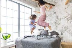 Mère et fille sautant sur le lit Photographie stock
