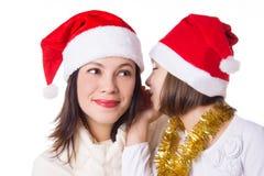 Mère et fille se partageant secrets le réveillon de Noël Photo stock