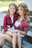 Mère et fille se reposant en parc d'été Photographie stock