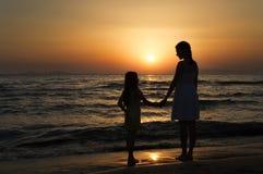 Mère et fille se tenant au coucher du soleil et regardant l'un l'autre Images stock