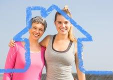 Mère et fille se tenant dehors contre le contour de maison à l'arrière-plan images libres de droits