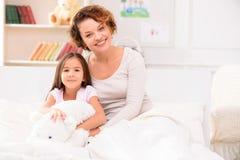 Mère et fille se trouvant sur le lit Image stock