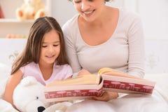 Mère et fille se trouvant sur le lit Photos libres de droits