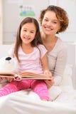Mère et fille se trouvant sur le lit Photos stock