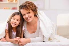 Mère et fille se trouvant sur le lit Images libres de droits