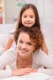 Mère et fille se trouvant sur le lit Images stock