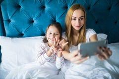 Mère et fille se trouvant sur le lit et prenant l'autoportrait avec le smartphone Femme prenant le selfie au téléphone avec une p Images stock