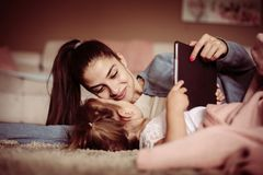 Mère et fille se trouvant sur le plancher et à l'aide du comprimé numérique images libres de droits