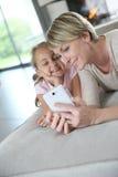 Mère et fille souriant et à l'aide du smartphone Images libres de droits