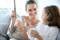 Mère et fille souriant et mangeant du yaourt Photos libres de droits