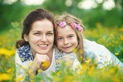 Mère et fille sur le pré de ressort avec les fleurs de floraison photos stock