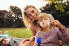Mère et fille sur un pique-nique au parc images stock