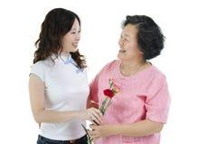Mère et fille tenant la fleur et le sourire d'oeillet Images stock