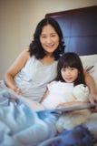 Mère et fille tenant le livre sur le lit dans la chambre de lit Photos stock