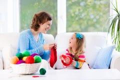 Mère et fille tricotant l'écharpe de laine Image libre de droits
