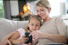 Mère et fille websurfing sur le smartphone Image libre de droits