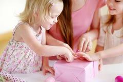 Mère et filles de het deux enveloppant un cadeau Photo stock