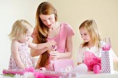 Mère et filles de het deux enveloppant un cadeau Photos libres de droits