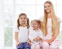 Mère et filles jouant dans la chambre à coucher pendant le jour de mère Images libres de droits