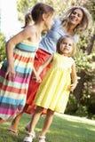 Mère et filles jouant dans le jardin Photos stock