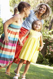 Mère et filles jouant dans le jardin Image libre de droits