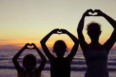 Mère et filles jouant sur la plage au temps de coucher du soleil Images stock