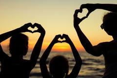 Mère et filles jouant sur la plage au temps de coucher du soleil Image stock