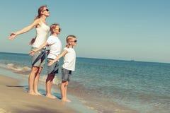 Mère et filles jouant sur la plage au temps de jour Image stock