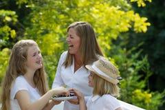 Mère et filles riant tout en mangeant des baies dehors Images stock