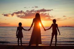 Mère et filles se tenant sur la plage au temps de coucher du soleil Photo stock
