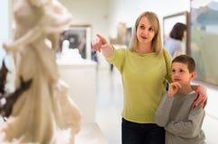 Mère et fils appréciant des expositions dans le musée image libre de droits