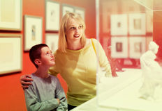 Mère et fils appréciant des expositions dans le musée Photographie stock
