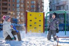 Mère et fils appréciant le beau jour d'hiver dehors, jouant avec la neige dans la ville Image libre de droits