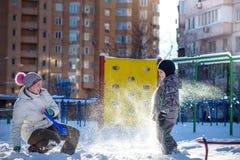 Mère et fils appréciant le beau jour d'hiver dehors, jouant avec la neige dans la ville Photographie stock