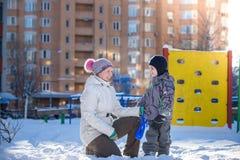 Mère et fils appréciant le beau jour d'hiver dehors, jouant avec la neige dans la ville Photo stock