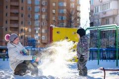 Mère et fils appréciant le beau jour d'hiver dehors, jouant avec la neige dans la ville Photo libre de droits