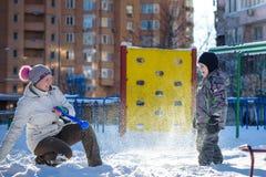 Mère et fils appréciant le beau jour d'hiver dehors, jouant avec la neige dans la ville Photos libres de droits