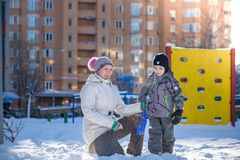 Mère et fils appréciant le beau jour d'hiver dehors, jouant avec la neige dans la ville Image stock