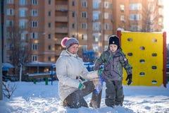 Mère et fils appréciant le beau jour d'hiver dehors, jouant W Images stock
