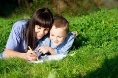 Mère et fils appréciant son écriture Image libre de droits