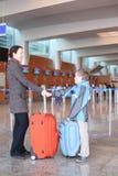 Mère et fils avec des valises dans le hall d'aéroport Image libre de droits