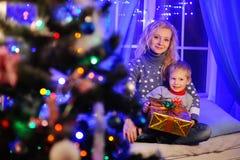 Mère et fils avec le cadeau de Noël à disposition sur le fond des lumières Photos stock